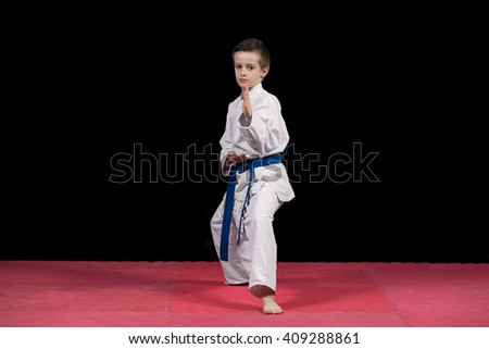 Portrait of a karate kid  in kimono ready to fight isolated on black background. - stock photo
