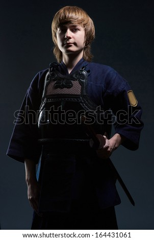 portrait of a kendo fighter with bokken, dark background - stock photo
