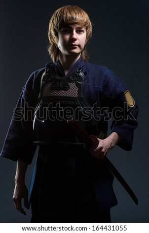 portrait of a kendo fighter with bokken on the dark background - stock photo
