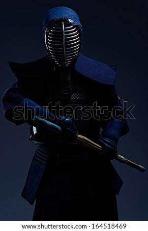 portrait of a kendo fighter with shinai, black background - stock photo