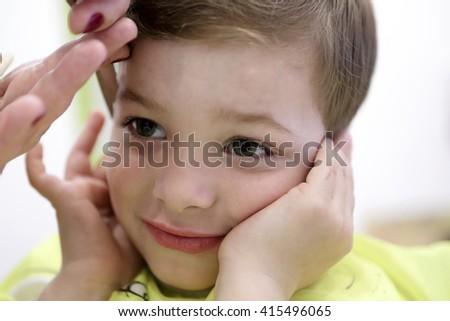 Portrait of a kid at hairdresser salon - stock photo