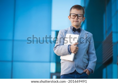 Portrait of a kid businessman on the modern background - stock photo