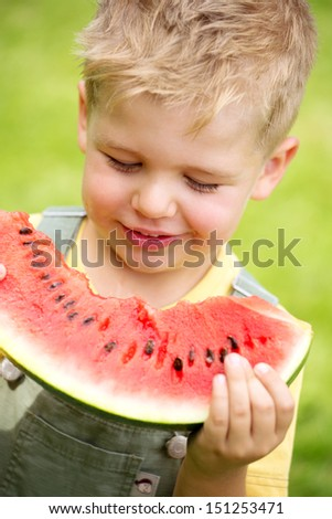 portrait of a kid eating a slice of watermelon - stock photo