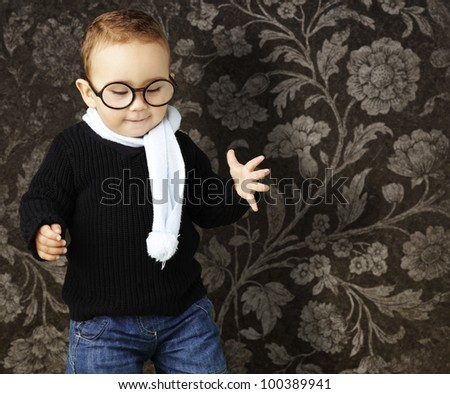 portrait of a kid wearing glasses looking down agaisnt a vintage background - stock photo