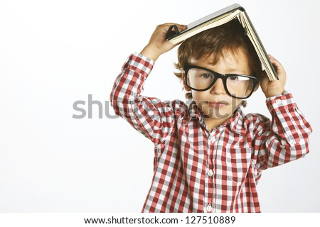 Portrait of a kid with rimmed glasses isolated on white. Child who wears plaid shirt with a book on his head - stock photo