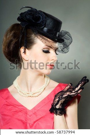 Portrait of a lady in a hat with veil, beads and lace gloves. Retro - stock photo