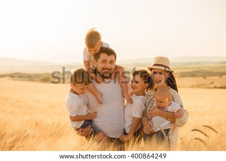 Portrait of a large family, a field of wheat, summer landscape, happiness - stock photo