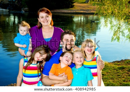 Portrait of a large family with five young children.  All are dressed in bright colors and they are standing by a lake.  Most have big smiles or are laughing. - stock photo