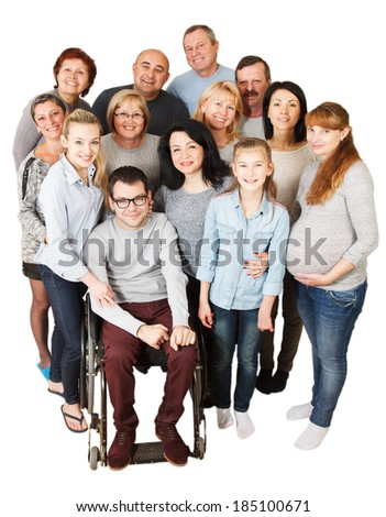 Portrait of a large group of a Mixed Age people smiling and embracing together with Disabled Man. - stock photo