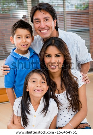 Portrait of a Latin family smiling at home looking very happy  - stock photo