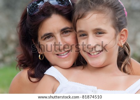 Portrait of a latin mother and daughter smiling together - stock photo