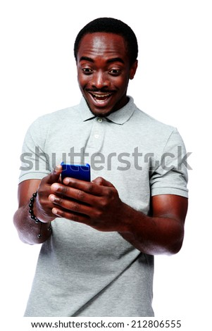Portrait of a laughing african man using smartphone over white background - stock photo