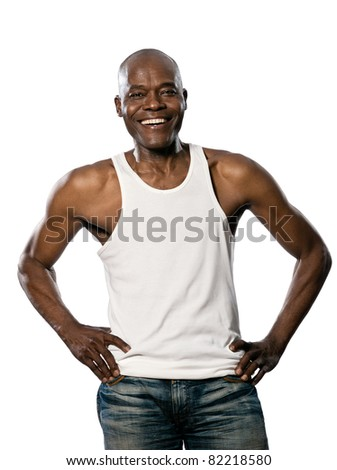 Portrait of a laughing afro American mature man with hands on waist standing in studio on white isolated background - stock photo