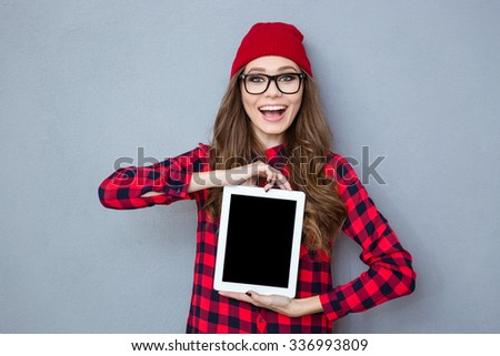 Portrait of a laughing casual woman showing blank tablet computer screen on gray background - stock photo