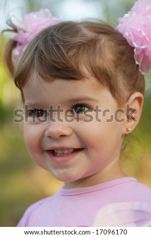Portrait of a laughing cute little girl with pink bows