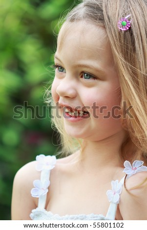 Portrait of a laughing little girl in the sunlight.