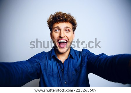 Portrait of a laughing man over blue background - stock photo