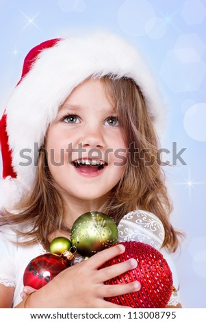 Portrait of a laughing preschool girl in Santa hat holding Christmas decoration in hands - stock photo
