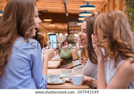 Portrait of a laughing woman showing something on smartphone screen to her girlfriends in cafe - stock photo