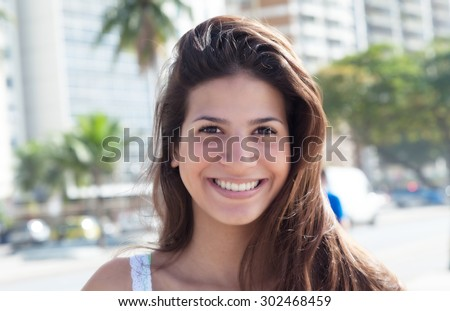 Portrait of a laughing woman with dark hair in the city - stock photo
