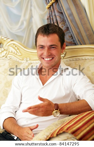 Portrait of a laughing young guy enjoying conversation with somebody - stock photo