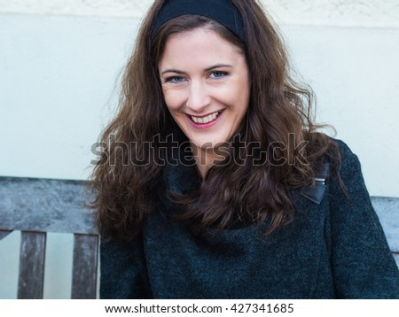 Portrait of a laughing young woman sitting on a bench outside