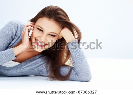 Portrait of a laughing young woman talking on mobile phone - stock photo