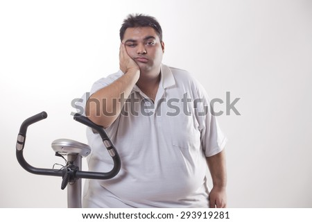 Portrait of a lazy obese man with an exercise bike over white background - stock photo