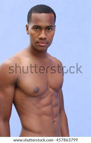 Portrait of a lean toned and ripped muscle fitness man under soft lighting - stock photo
