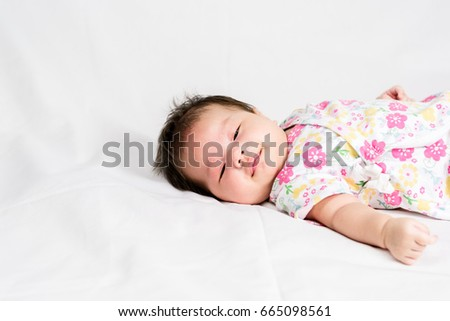 Portrait of a little adorable infant baby girl lying on the back on the bed