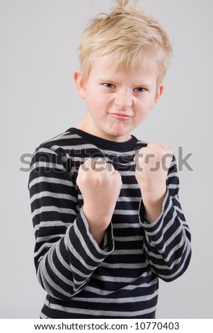 Portrait of a little angry boy standing in fight position - stock photo