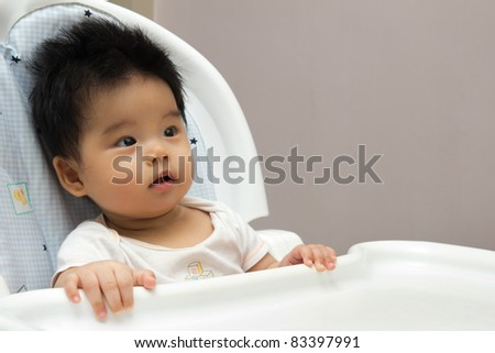 Portrait of a little Asian baby girl sits on a high chair