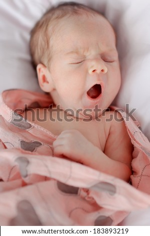 portrait of a little baby in a blanket colored sweet yawns