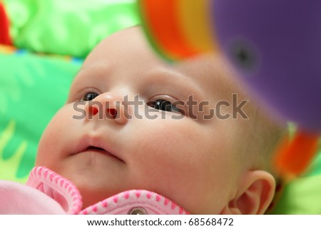 Portrait of a little baby surrounded by toys - stock photo