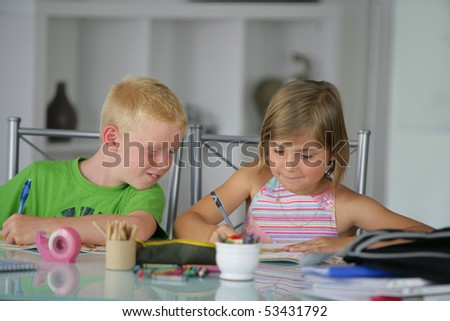 Portrait of a little boy and a little girl doing homework - stock photo