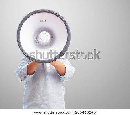 portrait of a little boy covering his face with a megaphone - stock photo
