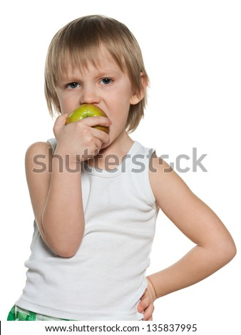 Portrait of a little boy eating an apple on the white background - stock photo