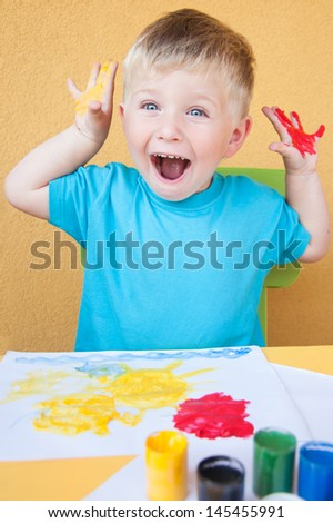 Portrait of a little boy enjoying his painting - stock photo
