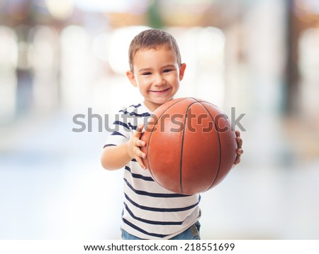portrait of a little boy holding a basket ball - stock photo