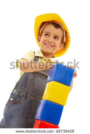 Portrait of a little boy in helmet with a tower of blocks - stock photo