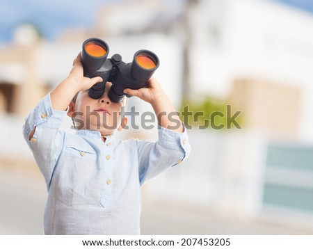 portrait of a little boy looking through the binoculars - stock photo