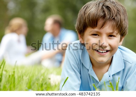 Portrait of a little boy lying on grass, looking at camera and smiling