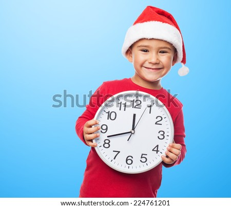 portrait of a little boy on christmas time holding a big clock - stock photo