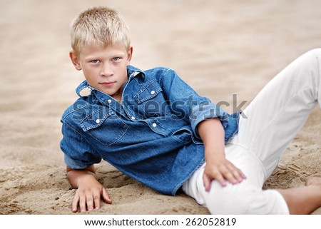 portrait of a little boy on the beach in summer - stock photo