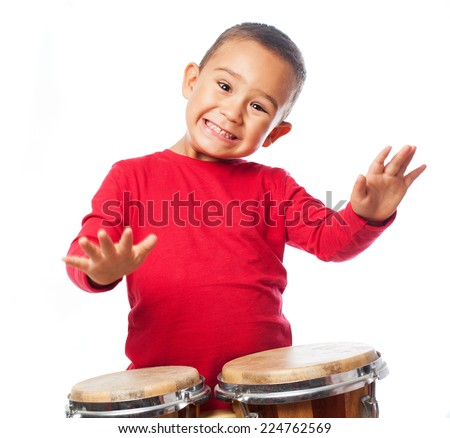 portrait of a little boy playing bongos - stock photo