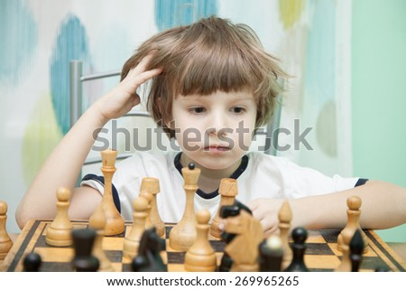 Portrait of a little boy playing chess - stock photo