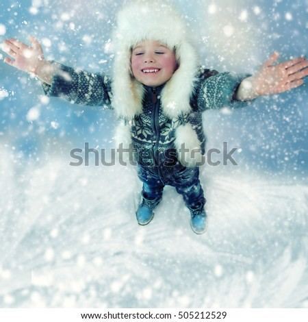 Portrait of a little boy playing outdoors in the snow. Top view.