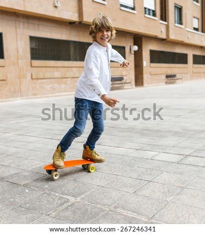 Portrait of a little boy practicing skateboard - stock photo
