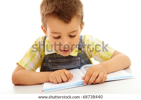 Portrait of a little boy reading a book isolated on white