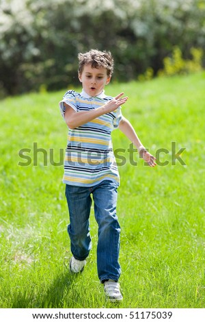 Portrait of a little boy running on a meadow